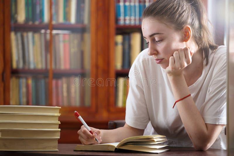 La jeune fille lit un livre à la bibliothèque photographie stock libre de droits