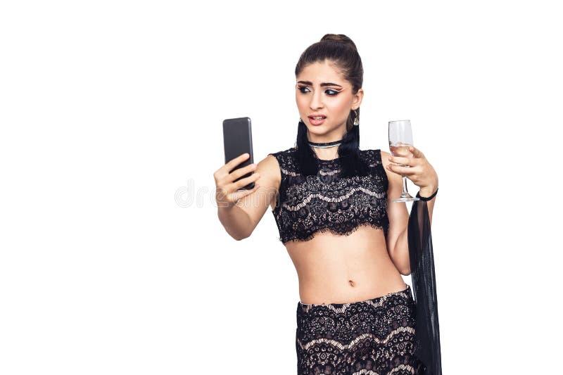 La jeune fille magnifique tient un verre de champagne et selfie de prise photos stock
