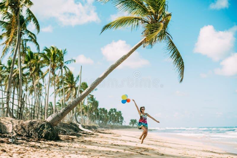 La jeune fille marche sur la plage image stock