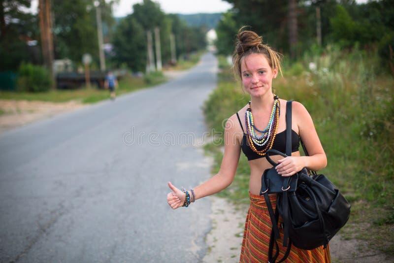 La jeune fille mignonne arrête la voiture près de la route Voyage image libre de droits