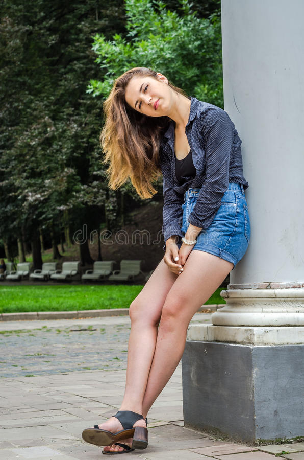 La jeune fille mignonne avec de longs cheveux dans une chemise et un denim court-circuite la marche en parc dans le jour d'été en photographie stock