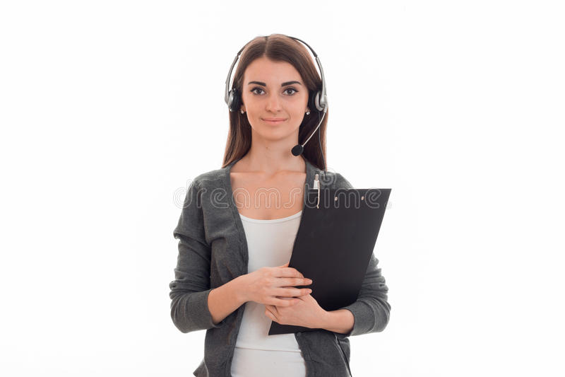 La jeune fille mignonne semble la bonne position avec les écouteurs et la participation une Tablette pour des valeurs images stock