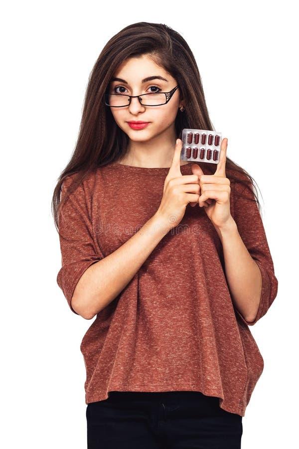 La jeune fille montre la boursouflure avec des capsules Industrie pharmaceutique photographie stock