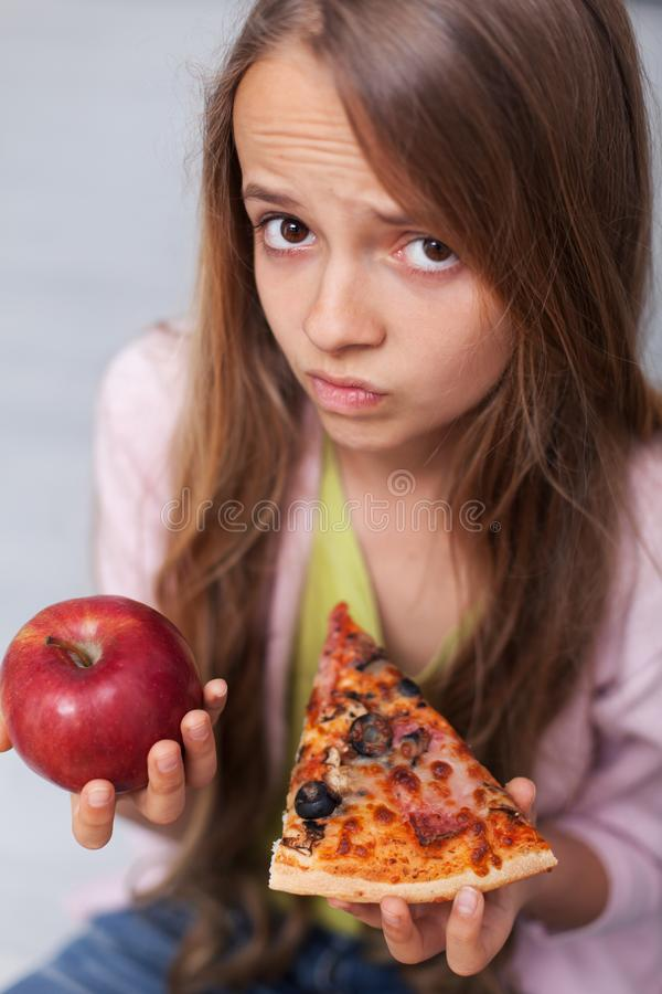 La jeune fille ne peut pas décider entre la pizza appétissante et la pomme saine image stock