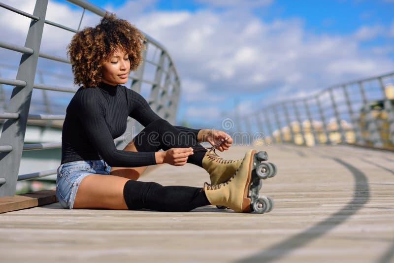 La jeune fille noire s'asseyant sur le pont urbain et met dessus des patins Femme avec le roller Afro de coiffure le jour ensolei photos stock