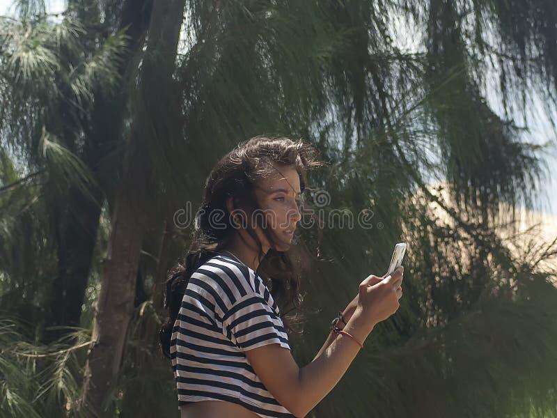 La jeune fille parle joyeux le téléphone photo stock