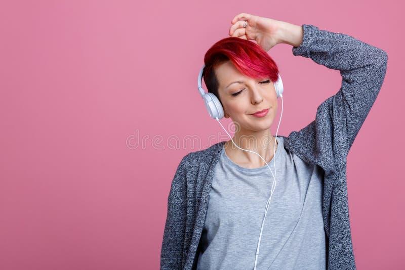 La jeune fille, a plaisir à écouter la musique sur des écouteurs Sur un fond rose image stock