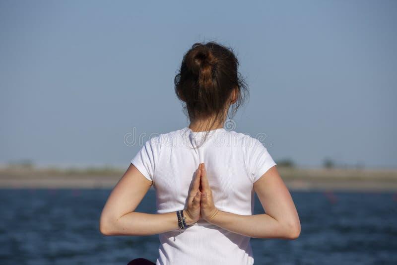 La jeune fille pratique le yoga sur le rivage du lac, le concept d'appr?cier l'intimit? et la concentration, lumi?re du soleil images libres de droits