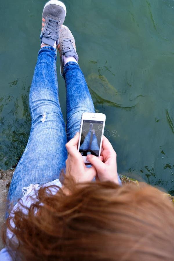La jeune fille prenant des photos avec un téléphone au voient image libre de droits