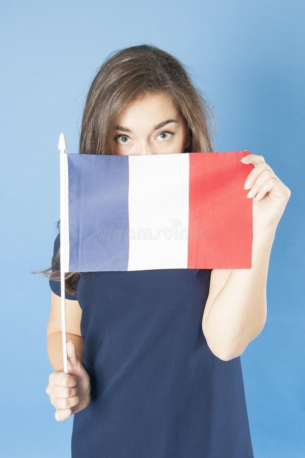 La jeune fille regarde hors du drapeau français image stock
