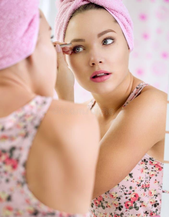 La jeune fille retirent des sourcils avec des brucelles image stock
