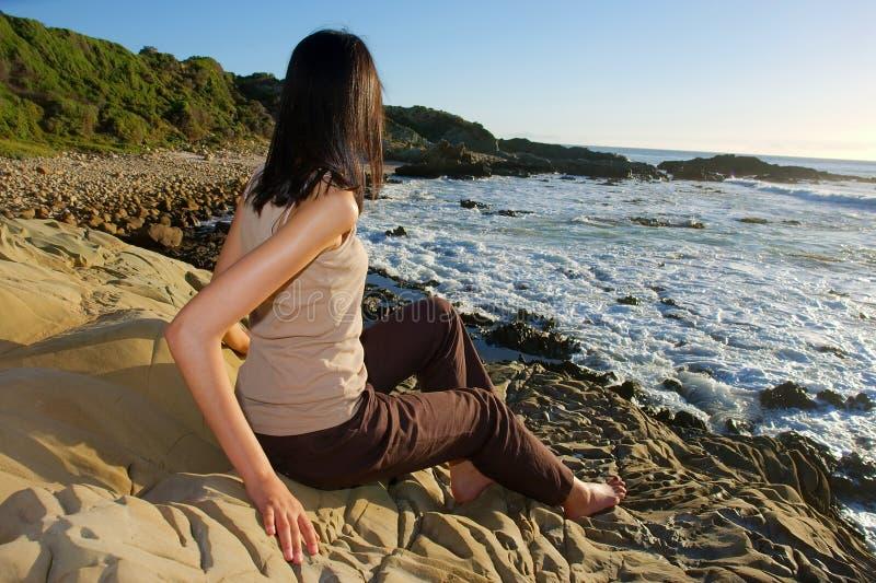La jeune fille s'assied sur des roches et regarde la mer photo stock