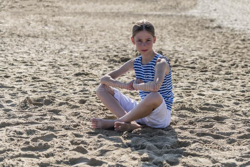 La jeune fille s'assied sur la plage photo stock