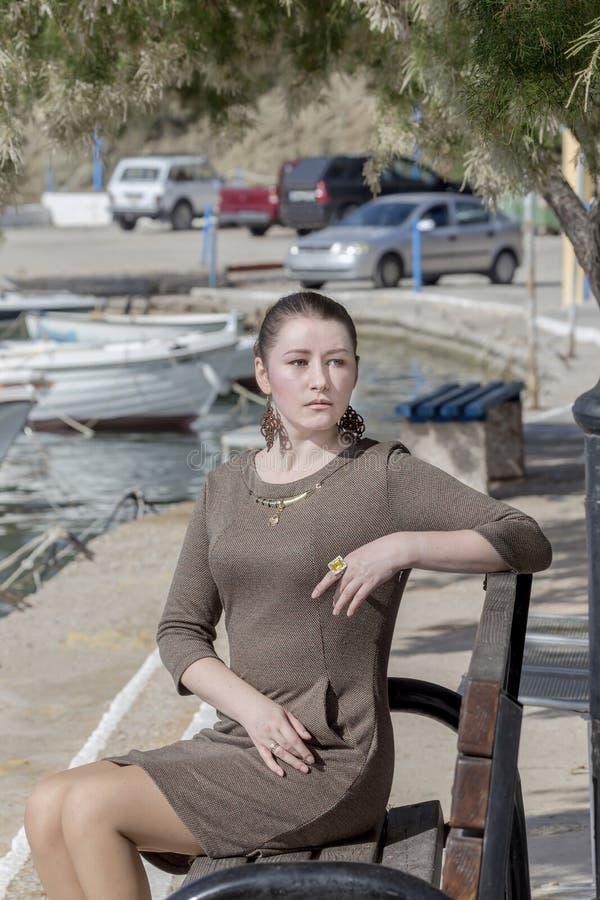 La jeune fille s'assied sur un plan rapproché de banc image libre de droits