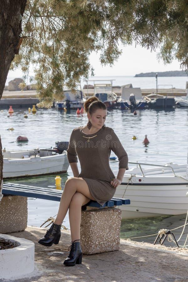 La jeune fille s'assied sur un plan rapproché de banc images stock