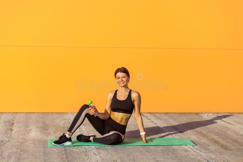 La jeune fille satisfaisante portant l'exercice de pratique de sport de sporwear noir sur la rue, se reposant sur des bandes, ont photo libre de droits