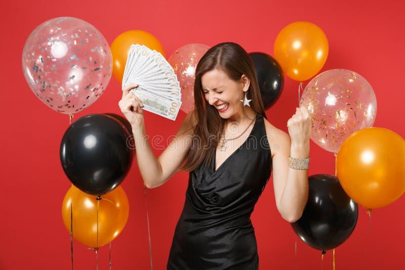 La jeune fille satisfaite dans un bon nombre noirs de paquet de participation de robe de dollars encaissent l'argent faisant le g photographie stock libre de droits