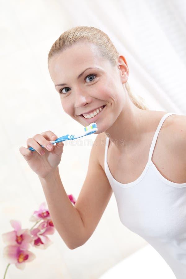 La jeune fille se brosse les dents photos stock