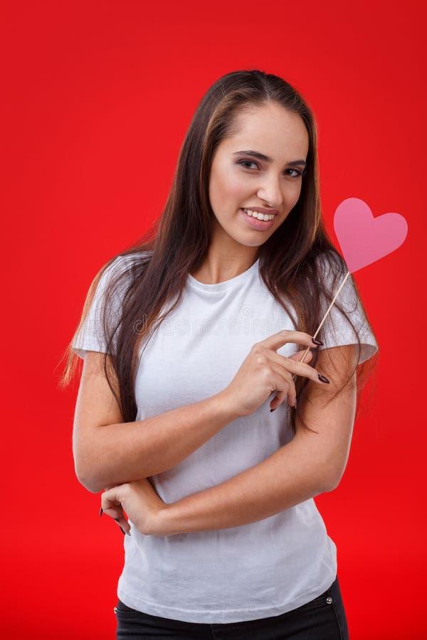 La jeune fille se tient avec un regard gêné, un sourire mignon et des prises un petit coeur de papier rose sur un bâton photos libres de droits