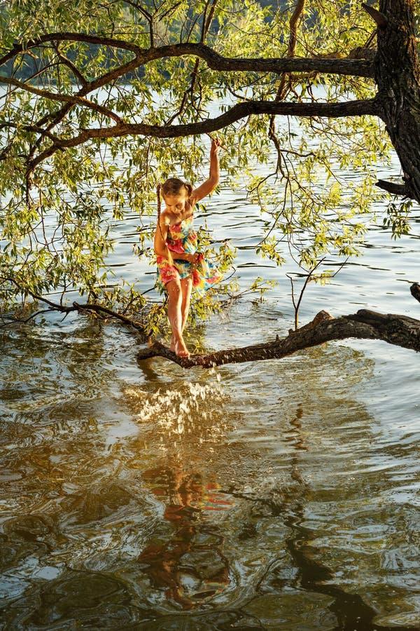 La jeune fille se tient sur une branche d'un arbre au-dessus de l'eau d'une rivière et éclabousse son pied photo libre de droits