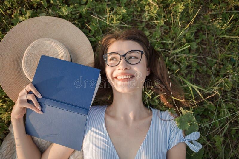 La jeune fille se trouve sur l'herbe Attrayant et lumineux heureux photographie stock libre de droits