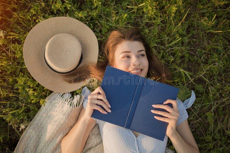 La jeune fille se trouve sur l'herbe Attrayant et lumineux heureux photo libre de droits