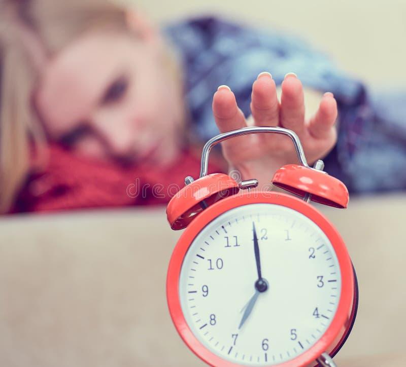 La jeune fille se trouve sur le divan et étire sa main au réveil rouge pour l'arrêter Réveillez-vous tard image stock