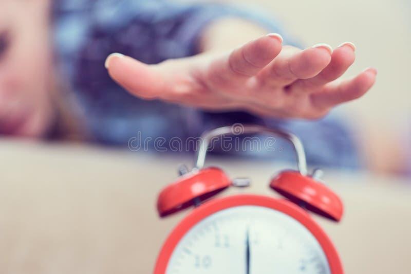 La jeune fille se trouve sur le divan et étire sa main au réveil rouge pour l'arrêter Réveillez-vous tard photographie stock