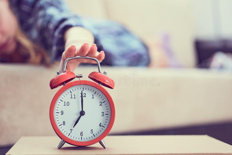 La jeune fille se trouve sur le divan et étire sa main au réveil rouge pour l'arrêter Réveillez-vous tard photo libre de droits