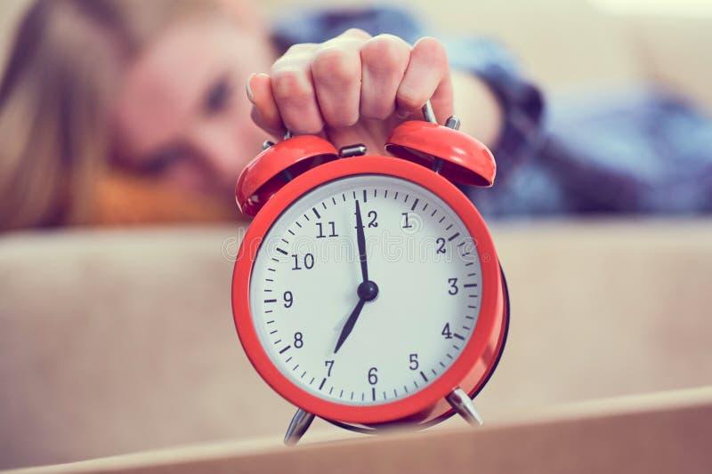 La jeune fille se trouve sur le divan et étire sa main au réveil rouge pour l'arrêter Réveillez-vous tard images libres de droits