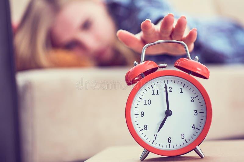 La jeune fille se trouve sur le divan et étire sa main au réveil rouge pour l'arrêter Réveillez-vous tard photos libres de droits