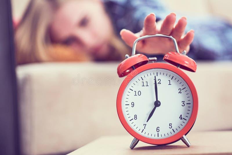 La jeune fille se trouve sur le divan et étire sa main au réveil rouge pour l'arrêter Réveillez-vous tard photographie stock libre de droits