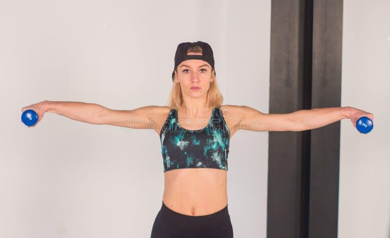 La jeune fille sexy d'athlétisme faisant des haltères pressent des exercices La forme physique muscled la femme dans la séance d' image stock