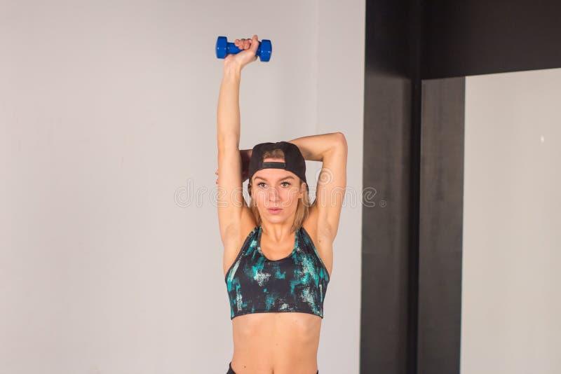 La jeune fille sexy d'athlétisme faisant des haltères pressent des exercices La forme physique muscled la femme dans la séance d' photographie stock libre de droits