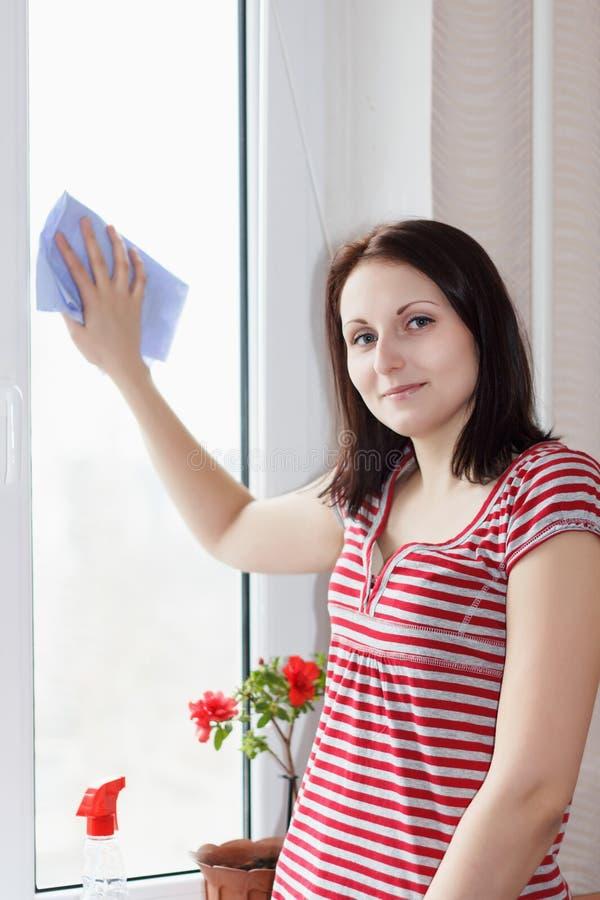 La jeune fille soigneuse lave et nettoie une fenêtre images libres de droits