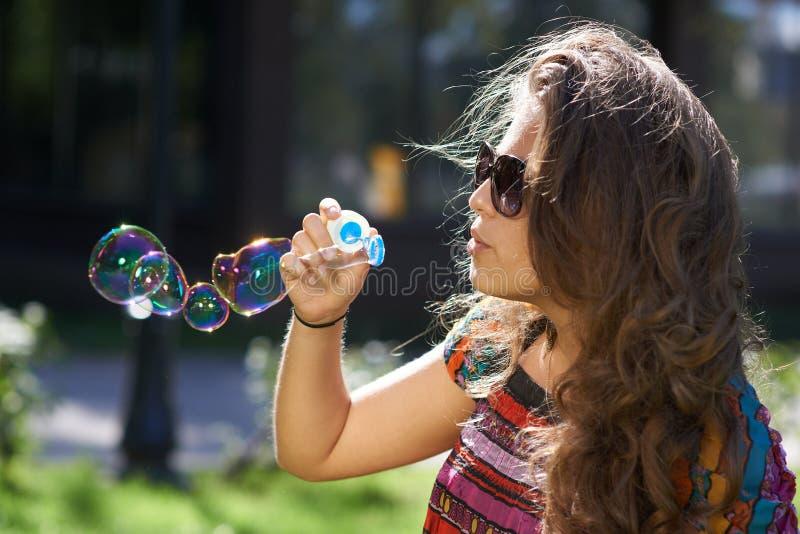 La jeune fille souffle des bulles de savon images stock