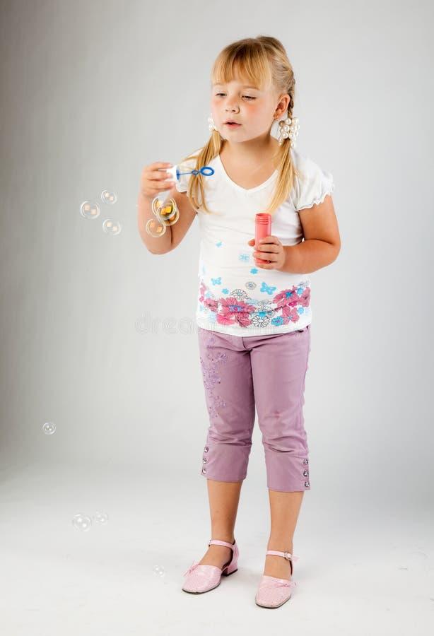 La jeune fille soufflent des bulles de savon images stock