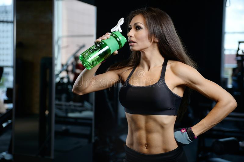 La jeune fille sportive sexy prend la nutrition de sport image stock