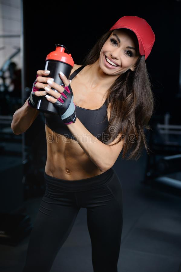 La jeune fille sportive sexy prend la nutrition de sport images stock