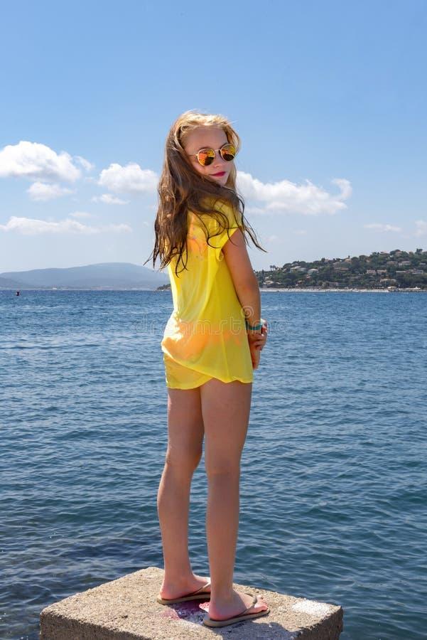 La jeune fille, supports sur une pierre, regardant au-dessus de la mer Méditerranée et tourne sa tête au photographe image libre de droits