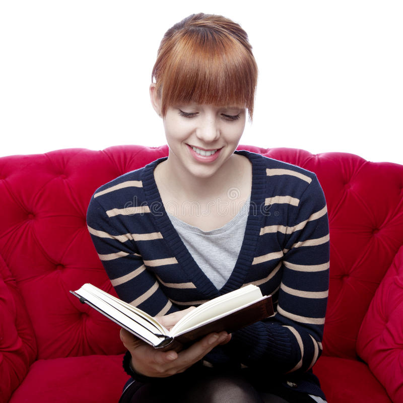 La jeune fille sur le sofa rouge a affiché un livre image libre de droits