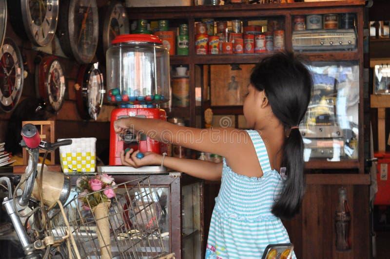 La jeune fille thaïlandaise obtient la sucrerie d'une vieille machine dans un magasin de cru image libre de droits