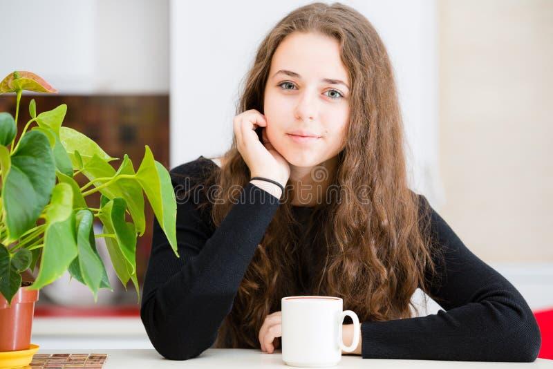 La jeune fille tient une tasse photographie stock libre de droits