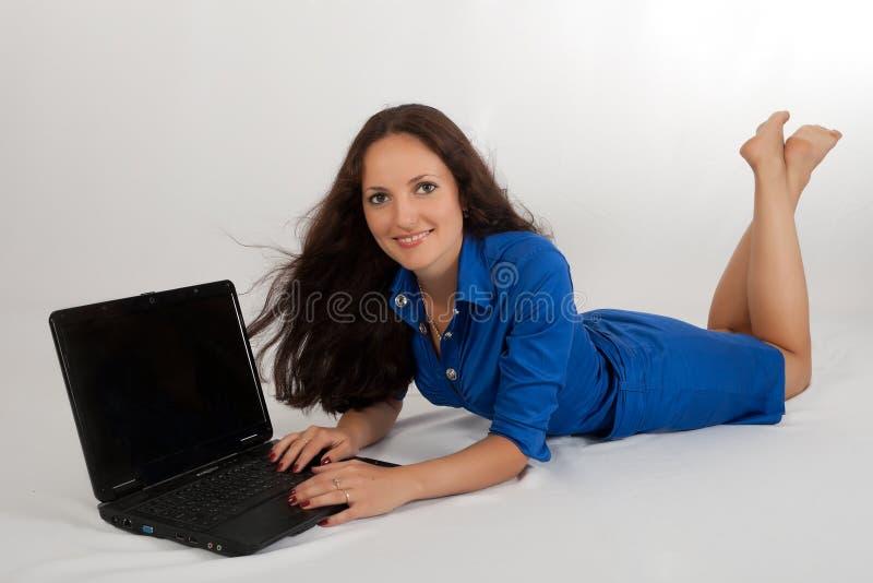 La jeune fille travaille sur l'ordinateur portatif. images libres de droits