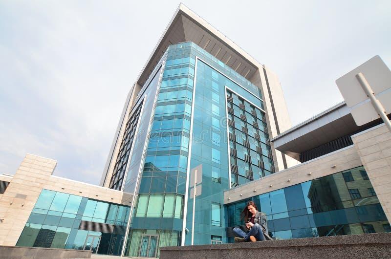 La jeune fille utilise un smartphone sur le fond d'immeuble de bureaux photo libre de droits