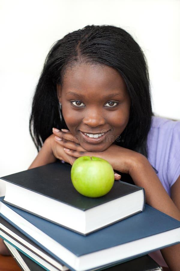 La jeune fixation d'étudiant réserve le sourire à l'appareil-photo photographie stock libre de droits