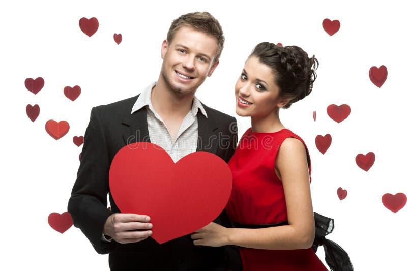 La jeune fixation de couples signent dedans la forme du coeur rouge photos stock