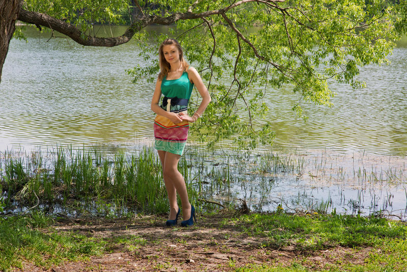 La jeune gentille fille mince dans une ombre d'arbre photo stock