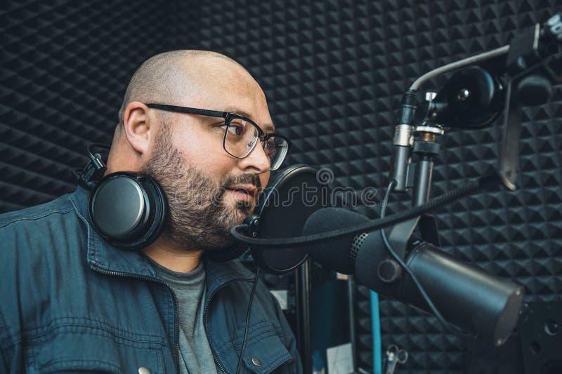 La jeune graisse et le présentateur ou l'hôte ou le DJ par radio chauve en verres avec des écouteurs autour de son cou parle dans image libre de droits