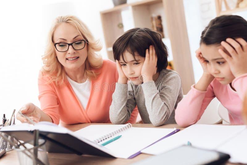 La jeune grand-mère aide à faire des leçons pour des petits-enfants Les beaux enfants d'aides de mamie apprennent photo libre de droits
